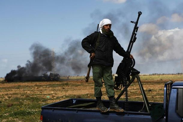 Waiting: a Libyan rebel stands as wreckage caused by a NATO attack burns behind him (Photo: Reuters)