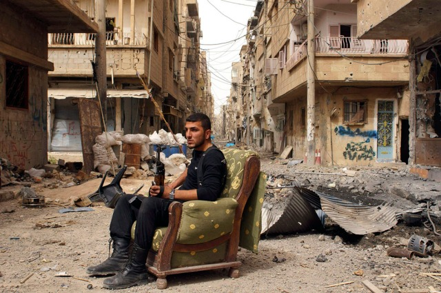 A member of the Free Syrian Army sits amidst rubble in Deir al-xor (Photo: Khalil Ashawi / Reuters)
