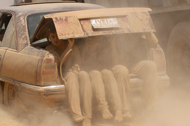 Young men are covered in dust as they flee violence in northern Iraq (Photo: Rodi Said / Reuters)