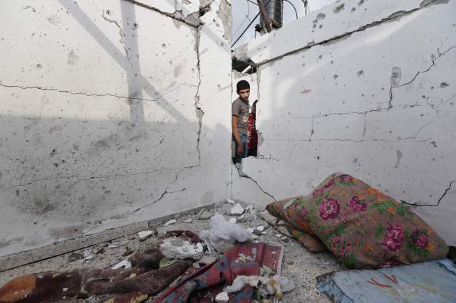 A young Palestinian examines damages to house in the Jebaliya refugee camp that had been hit by an Israeli strike. (The Associated Press)