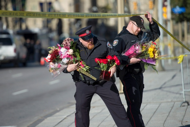 Police officers in Ottawa move flowers to the War Memorial (Photo: Justin Tang/Canadian Press)