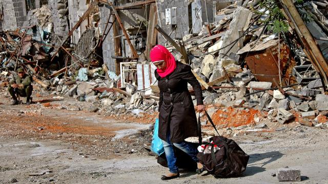 A woman carrying her belongings returns to her home in central Homs (Photo: European Pressphoto Agency)