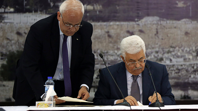 Palestinian Authority President Mahmoud Abbas recently signing a number of international treaties, including the Rome Statute (Photo: EPA)