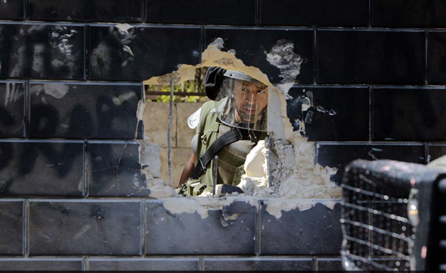 An Israeli security officer peers through a damaged part of the separation wall between Israel and Palestine (Photo: Abbas Momani / AF)