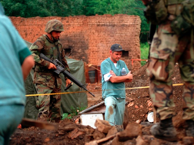 U.S. soldiers provide security as members of the Royal Canadian Mounted Police Forensics Team investigate a grave site in a village in Kosovo in 1999.  (Photo: Sgt. Craig J. Shell, U.S. Marine Corps)