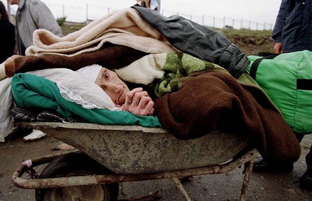A man pushes his ailing grandmother in a wheelbarrow to Albania during the Kosovo war.