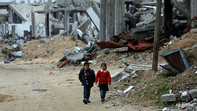 Children walk along a street in a heavily damaged neighbourhood in Gaza (Photo: AP)