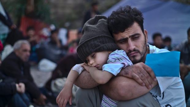 A Syrian man holds his son at a refugee camp (Photo: Muhammed Muheisen / Associated Press