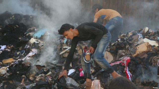 Citizens of Aleppo salvage goods from an aid convoy that had recently been bombed. (Photo: Reuters)