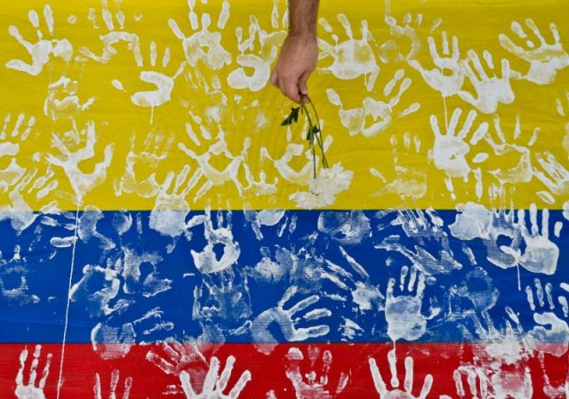 A man places a flower on a Colombian flag (Photo: Luis Robayo / AFP)