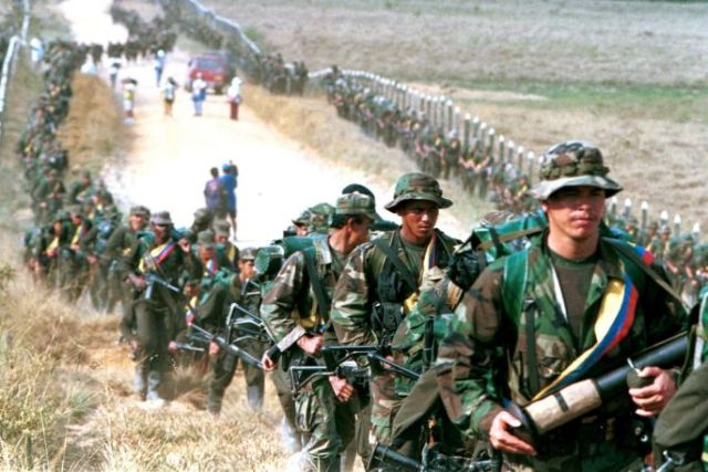 FARC troops patrol a roadway near to San Vicente de Caguan, in 1999. (Photo: Reuters)