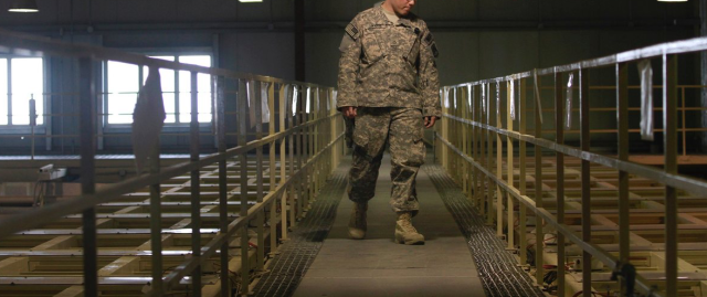 An American military guard looks over detainee cells at a detention facility near Bagram Air Field.(Photo: Dar Yasin / AP)